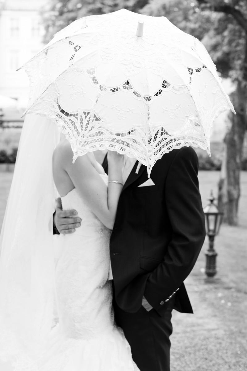 weißer Schirm aus Spitze, Bride and Groom, Kissing, lace umbrella